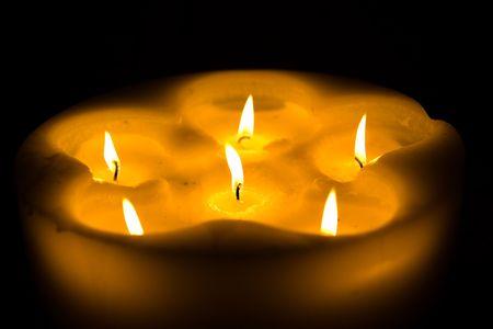 warmness: Some nice candles illuminating the dark room Stock Photo