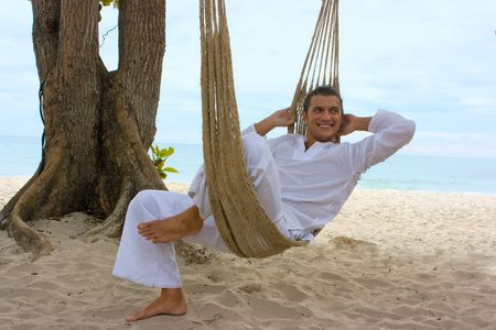 Young man relaxing on the sand beach Stock Photo