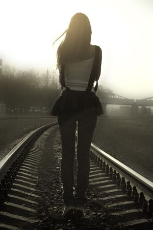 back light: Girl standing on the railway in the sunset beams