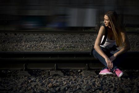 スニーカー: レールの上に座って彼女ピンクの gymshoes で若いブルネットのモデル