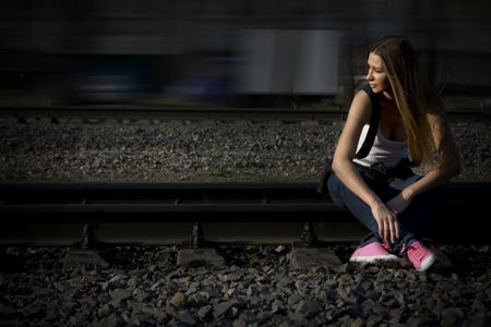 sneakers: Young brunette model in her pink gymshoes sitting on rails Stock Photo