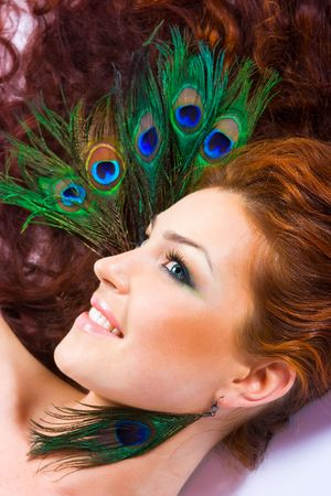 Red haired girl with peacock feather earings