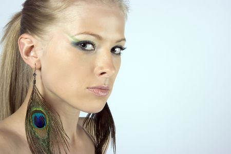 Close-up beautiful young blond model with peacock earrings photo