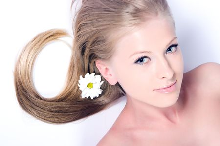 Beautiful blond girl with camomile flower in hair