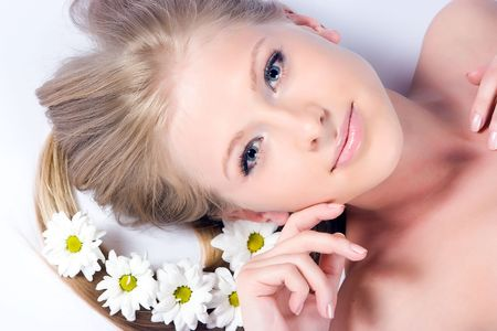 Beautiful blond girl with camomile flowers in hair