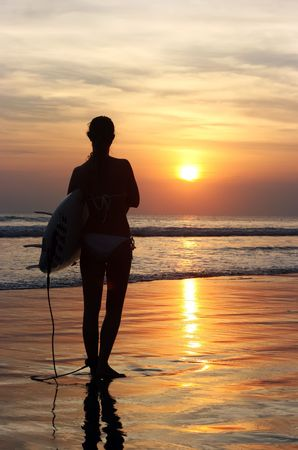 Surfer with board going into the sea at dawn Stock Photo