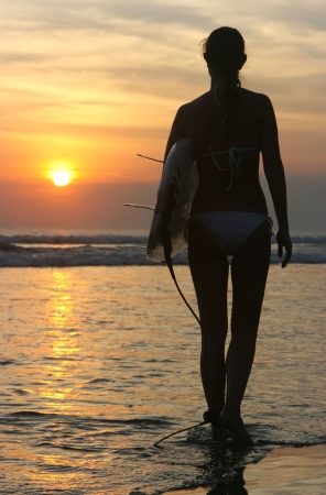 Silhouette of a surfer girl at sunset on Bali island photo