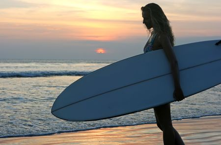 Silhouette of a girl with surf standing on the beach at sunset Stock Photo
