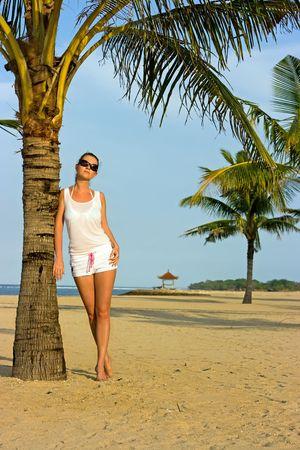 Brunette girl standing on the palm beach