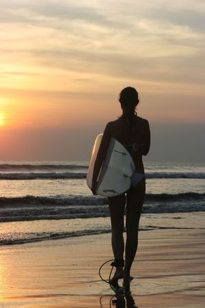 Silhouette of a girl with surf in front of the ocean at dawn photo