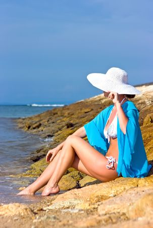 Brunette lady in blue shawl and white hat standing on the rocky beach photo
