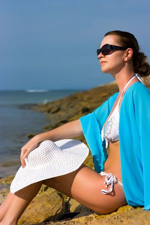 Brunette lady with white hat sitting on the rocky beach photo