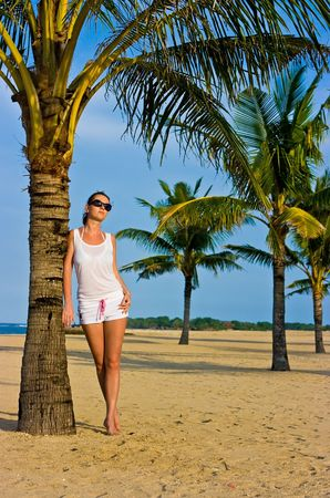 Beautiful brunette girl standing on the lonely sand beach leaning against the palm tree photo