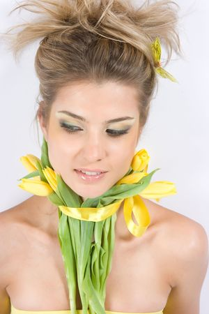 Close-up fresh funny blond with beautiful make-up with tulips photo