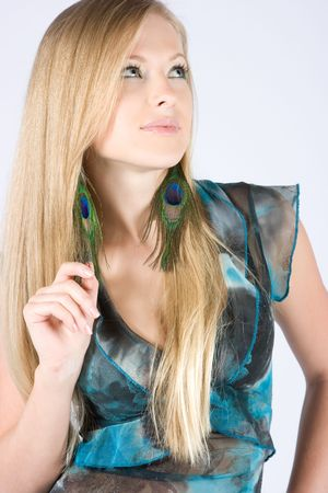 Beautiful young blond model with peacock earrings posing in studio shot photo