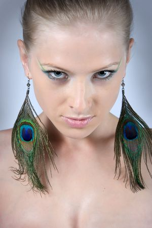 Close-up young blonde model with peacock earrings posing with beautiful make-up photo