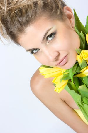 Close-up fresh blond lady with beautiful make-up with tulips photo
