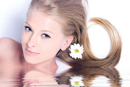 Beautiful blonde girl with camomile flower in hair Stock Photo
