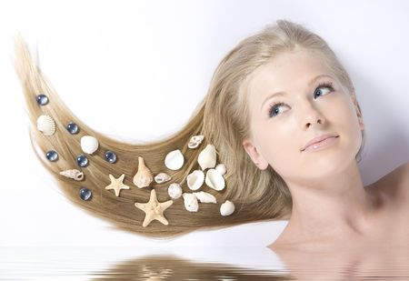 Close-up beautiful blond lying on white background with shell in her hair Stock Photo