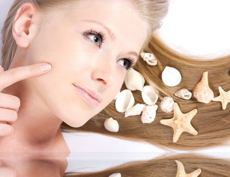 Close-up beautiful young fresh blonde lady with shells in her hair photo
