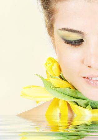 Close-up fresh funny blonde with beautiful make-up with tulips photo