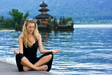 Beautiful blonde girl meditating at the lake