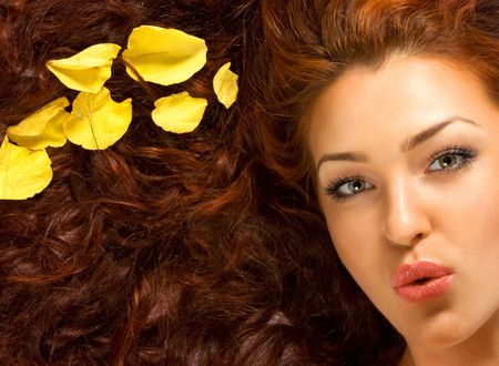 Close-up beautiful fresh luxury red-haired lady with yellow petals in her hair photo