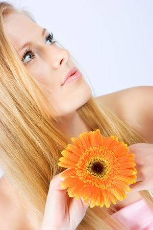 Close-up beautiful young fresh blonde lady with flower Stock Photo - 5303759