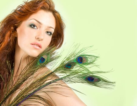 Beautiful red-haired women with peacock feathers in studio shot photo