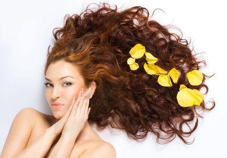 Close-up beautiful fresh luxury red-haired lady with yellow petals in her hair