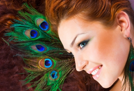 Close-up beautiful luxury red-hared model with perfect make-up with peacock feather in her hair and peacock earings
