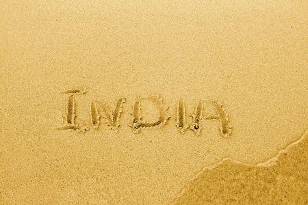 Word India written on sand beach photo