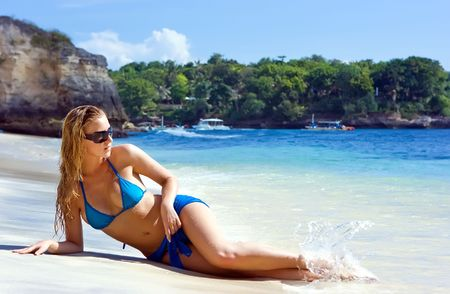 Blonde girl relaxing in water on the beach on Bali island in Indonesia photo