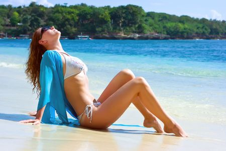 Beautiful brunette young girl relaxing on the sand beach on Bali island in Indonesia photo