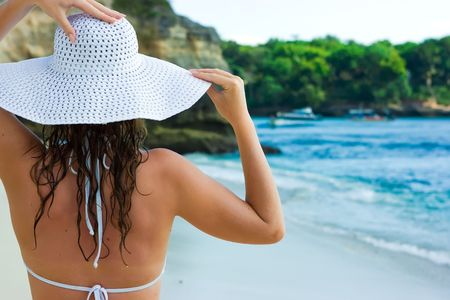 Beautiful brunette with long hair in white hat stands on the sand ocean beach on Bali in Indonesia photo