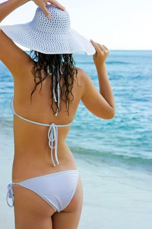 Beautiful brunette with long hair in white hat and swimsuit stands on the sand ocean beach on Bali in Indonesia photo