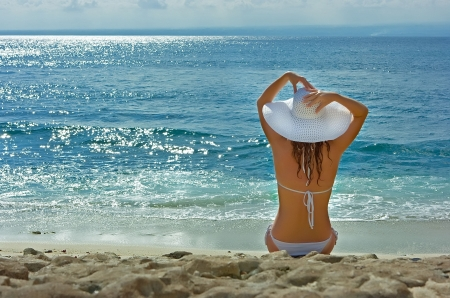 Beautiful brunette with long hair in white hat and swimsuit sits on the sand ocean beach on Bali in Indonesia