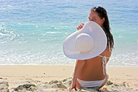 Beautiful brunette with long hair in white hat and swimsuit sits on the sand ocean beach on Bali in Indonesia photo