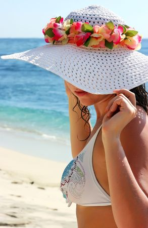 Beautiful brunette girl with long hair in white hat on the sand ocean beach on Bali in Indonesia photo