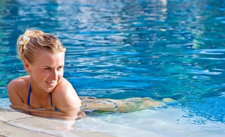 hotel indonesia: Beautiful blonde happy girl in hotel swimming pool with flower in long hair
