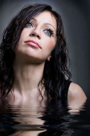 Young brunette girl with wet hair in studio shot photo