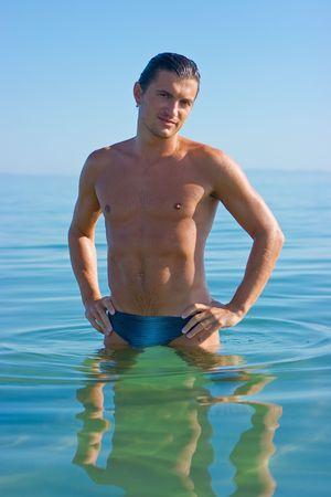 brune: Handsome brune man standing in sea water Stock Photo