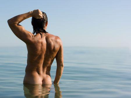 nalga: Young sexy hombre de pie muscular en el agua de mar en la neblina