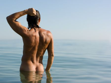 breech: Young sexy muscular man standing in sea water in haze