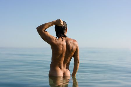 Young sexy muscular man standing in sea water in haze