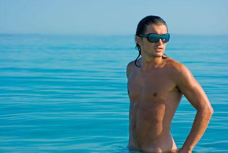 brune: Handsome muscular young man standing in sea water