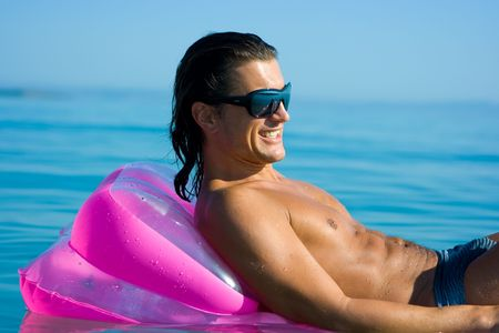 Handsome muscular young man floating on inflatable raft in sea water Stock Photo - 5322269