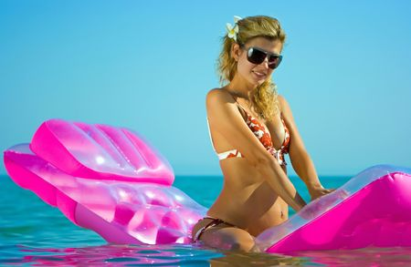 horizont: Beautiful blonde girl floating on inflatable raft in the sea