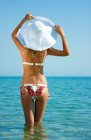 Beautiful blonde girl with white hat standing in sea water photo