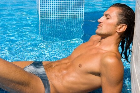 Young wet sexy muscular man lying relaxing in swimming pool